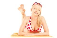 Menzogne femminile bionda sorridente su un asciugamano di spiaggia ed esaminare macchina fotografica Fotografie Stock Libere da Diritti