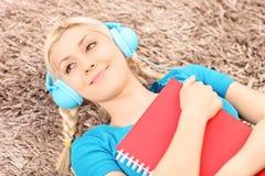 Menzogne femminile sorridente su un tappeto e su una musica d'ascolto Immagine Stock Libera da Diritti