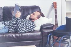 Menzogne invalida carismatica sul sofà e godere della lettura all'interno fotografia stock