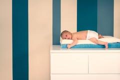 Menzogne neonata sveglia su un cassettone Fotografia Stock Libera da Diritti