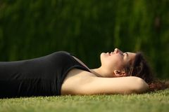 Menzogne rilassata della donna attraente sull'erba Fotografia Stock Libera da Diritti
