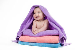 Menzogne sorridente del neonato su una pila di asciugamani Immagini Stock
