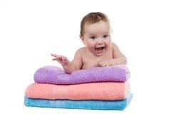 Menzogne sorridente del neonato su una pila di asciugamani Immagini Stock Libere da Diritti