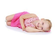 Menzogne sorridente della bambina sveglia sul pavimento fotografie stock libere da diritti