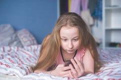 Menzogne teenager della ragazza sullo stomaco ed esaminare lo schermo del telefono Immagine Stock Libera da Diritti