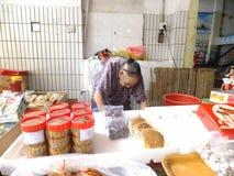 Mer än och 90 årig kinesisk gammal dam, försäljning av gods i marknaden Arkivfoton