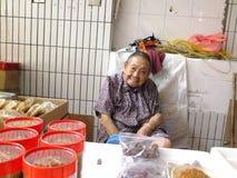 Mer än och 90 årig kinesisk gammal dam, försäljning av gods i marknaden Arkivfoto
