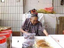 Mer än och 90 årig kinesisk gammal dam, försäljning av gods i marknaden Arkivbild