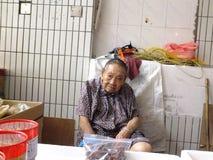 Mer än och 90 årig kinesisk gammal dam, försäljning av gods i marknaden Arkivbilder
