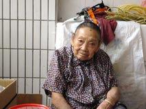 Mer än och 90 årig kinesisk gammal dam, försäljning av gods i marknaden Royaltyfri Bild