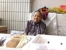 Mer än och 90 årig kinesisk gammal dam, försäljning av gods i marknaden Royaltyfri Fotografi