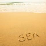 Mer - écrite à la main en sable sur une plage de mer, avec une vague molle Voyage Photos stock