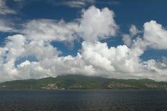Mer, île volcanique et nuages martinique images libres de droits