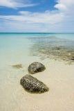 Mer agréable de roches en clair avec le ciel bleu et les nuages blancs à l'arrière-plan Images libres de droits