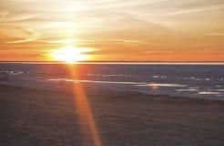 Mer baltique congelée et coucher du soleil Images stock