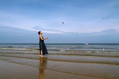 Mer baltique, femme dans les mouettes blanches de alimentation de robe d'été Images stock