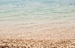 Mer bleu-clair peu profonde sur la plage de bardeau Images stock