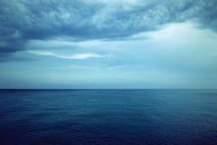Mer bleu-foncé et nuages orageux Images stock