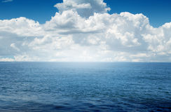 Mer bleue avec les nuages blancs Photographie stock