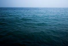 Mer bleue avec les vagues et le ciel clair Photo stock