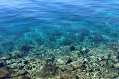 Mer bleue calme avec les roches clairement évidentes sur le fond allant de peu profond à l'extrémité profonde images stock