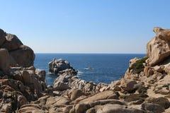 Mer bleue et ciel encadrés par les roches rouges sur la Sardaigne, Italie photographie stock
