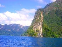 Mer bleue lumineuse, ciel clair de nuage, belle montagne Photo stock