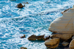 Mer bleue, roche jaune Photographie stock libre de droits
