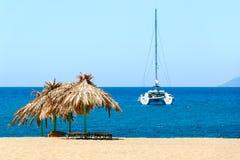 Mer bleue, sable d'or et lits pliants sur la plage Image libre de droits