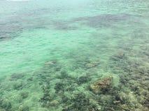 Mer bleue sur les roches le long de la côte Photographie stock