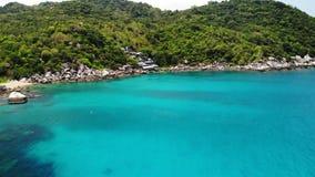 Mer calme près d'île volcanique tropicale Vue de bourdon de l'eau paisible de la mer bleue près du rivage pierreux et de la jungl banque de vidéos
