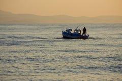 Mer d'or de bateau de coucher du soleil Images libres de droits