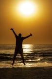 Mer d'homme de silhouette étreignant sauter de Sun Photographie stock