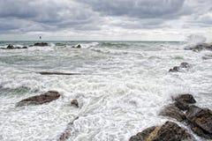 Mer dans la tempête sur des roches de village italien Image stock