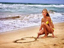 Mer de fille d'été La fille dans le maillot de bain écrivent sur la forme de coeur de sable Photo stock