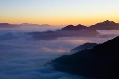 Mer de nuage dans le coucher du soleil Photographie stock