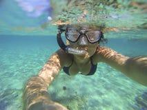 Mer de turquoise avec une plongée à l'air de jeune femme Image stock