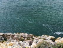 Mer de turquoise d'un côté rocheux d'une montagne photographie stock