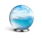 Mer et ciel bleus dans la boule en verre d'isolement sur le fond blanc, Photographie stock