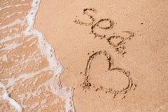 Mer et coeur dans le sable sur la plage Images stock