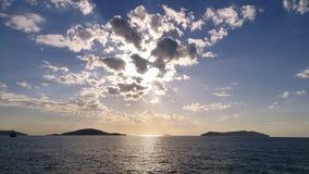 Mer et coucher du soleil avec des nuages image stock