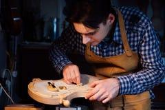 Mer luthier arbete för ledar- hantverkare på skapelsen av en fiol samvetsgrant detaljerat arbete på trä Arkivfoto