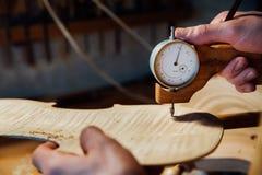 Mer luthier arbete för ledar- hantverkare på skapelsen av en fiol samvetsgrant detaljerat arbete på trä royaltyfri foto