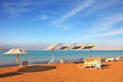 Mer morte, le sable orange et chaises de plage Image stock