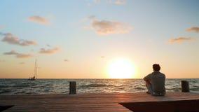 Mer nära blick på mannen som håller ögonen på solnedgången arkivfilmer
