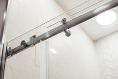 Mer nära metallstruktur av de övrehållarna och rullarna för dörren för glidningsexponeringsglas i duschen Royaltyfri Fotografi
