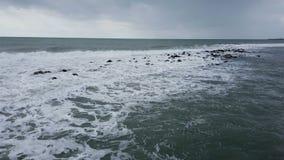 Mer orageuse et mousseuse avec des vagues se brisant sur les roches banque de vidéos