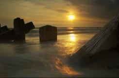 Mer, pôles et coucher du soleil Photo stock