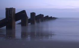 Mer, pôles et coucher du soleil Images stock