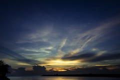 Mer pendant le coucher du soleil avec le ciel nuageux Photos stock